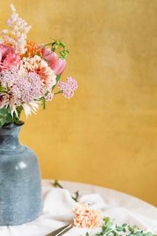 Bloemen in een vaas bij een gele muur