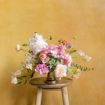 Bloemen in een vaas op een krukje