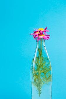 Bloemen in glazen fles op blauwe achtergrond