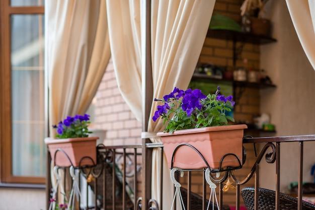 Bloemen in hangende potten op de veranda van het huis.