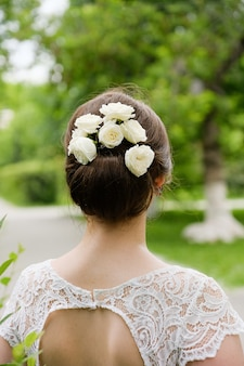 Bloemen in het haar van het meisje. achteraanzicht van elegante blonde bruid gekleed in witte jurk, buitenshuis. het concept van de bruiloft. de dag van de bruiloft, de ochtend van de bruid.