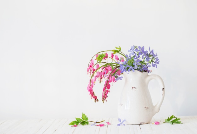 Bloemen in kruik op witte ruimte
