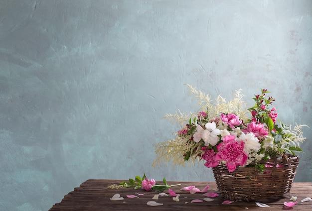 Bloemen in mand op oude houten tafel