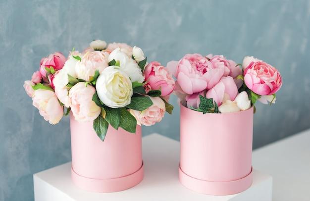 Bloemen in ronde luxe geschenkdozen. boeket van roze en witte pioenrozen in kartonnen doos. mock-up van hoedendoos met bloemen met gratis copyspace voor tekst. interieur in pastelkleuren.