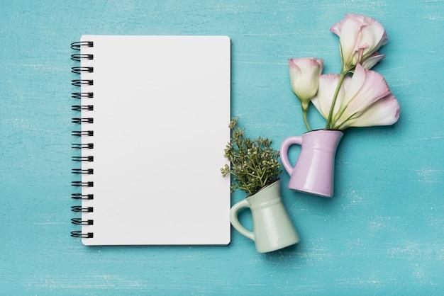 Bloemen in twee ceramische vazen met leeg spiraalvormig notitieboekje op blauwe houten achtergrond