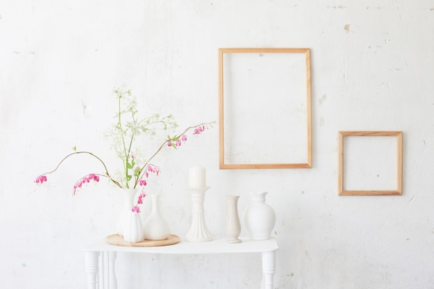 Bloemen in vaas en frames op de muur