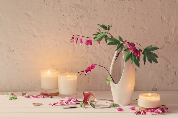 Bloemen in vaas met kaarsen op witte muur als achtergrond