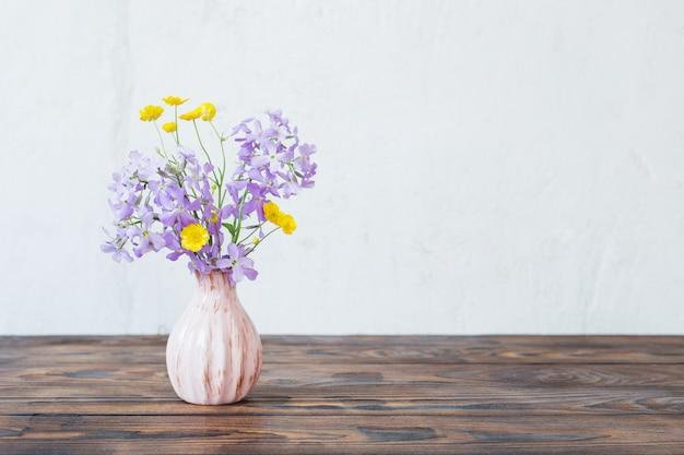 Bloemen in vaas op houten lijst aangaande witte muur als achtergrond