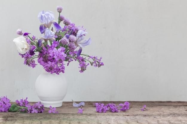 Bloemen in vaas op witte muur