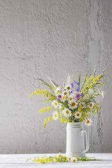Bloemen in witte kruik op wit