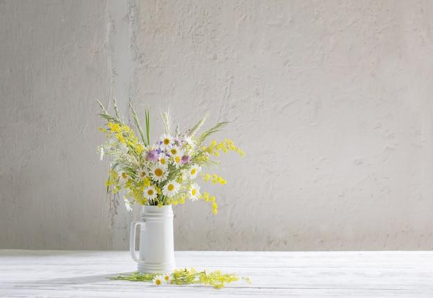 Bloemen in witte kruik op witte muur