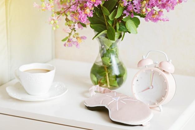 Bloemen, kopje koffie en wekker in de slaapkamer