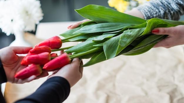 Bloemen levering. bloemist die een rood tulpenboeket schikt. vrouwenhanden binden een touwboog.