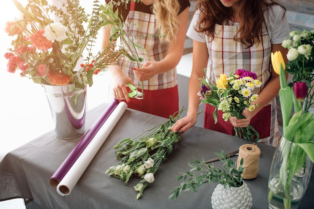 Bloemen levering bovenaanzicht. bloemisten die orde creëren, rozenboeket maken in bloemenwinkel. twee vrouwelijke bloemisten doen boeketten. een vrouw verzamelt rozen voor een stel, een ander meisje werkt ook.