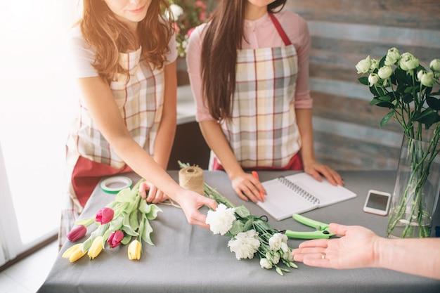 Bloemen levering bovenaanzicht. bloemisten die orde creëren, rozenboeket maken in bloemenwinkel. twee vrouwelijke bloemisten doen boeketten. en een klant bestelt bloemen boeket bloemenwinkel bloemist