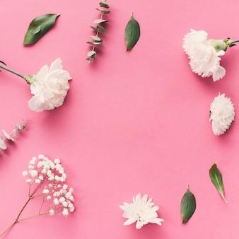 Bloemen met bladeren verspreid op tafel