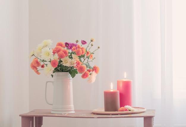 Bloemen met brandende kaarsen op vintage houten plank