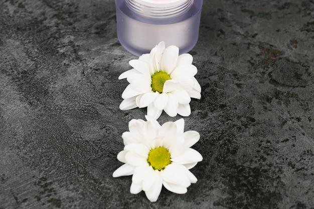 Bloemen met een potje crème op een donkere marmeren achtergrond. uitzicht van boven. natuurlijke cosmetica.