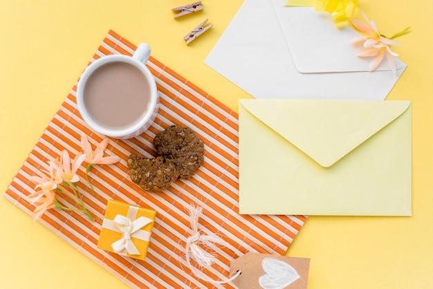 Bloemen met enveloppen, koffie en koekje