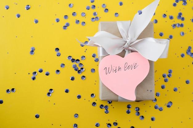Bloemen met ingepakt cadeau en met liefdeslabel