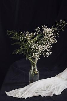 Bloemen met planten in vaas in de buurt van kralen op witte textiel