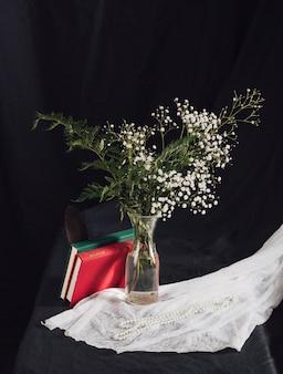 Bloemen met planten in vaas in de buurt van volumes en kralen op witte textiel op tafel
