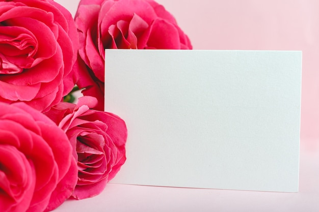Bloemen mockup felicitatie bruiloft uitnodigingskaart in boeket roze rode rozen op roze achtergrond