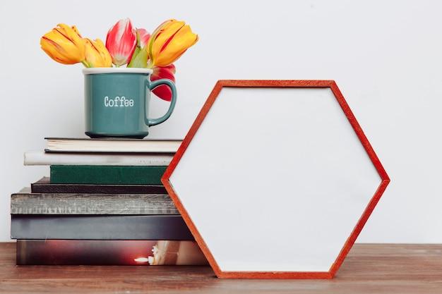 Bloemen op boeken dichtbij hexagon kader