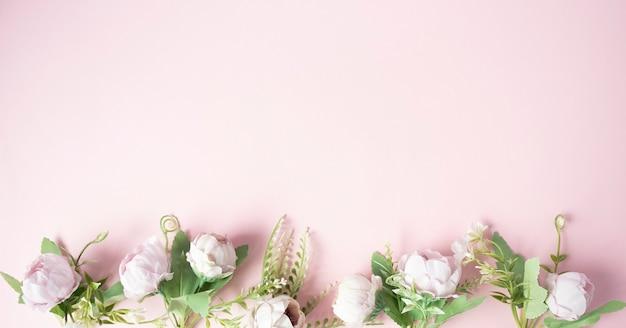 Bloemen op een roze achtergrond gerangschikt in een lijn vanaf de onderkant.