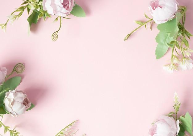 Bloemen op een roze achtergrond zijn gerangschikt in de hoeken van een roze achtergrond..