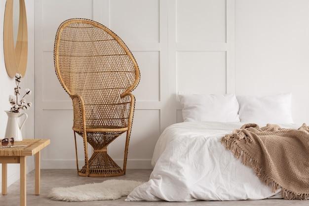 Bloemen op houten tafel naast rotan stoel in wit slaapkamer interieur met deken op bed