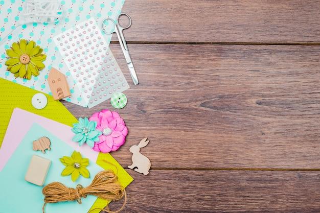 Bloemen; papier; parels; knop en draad met schaar op houten tafel