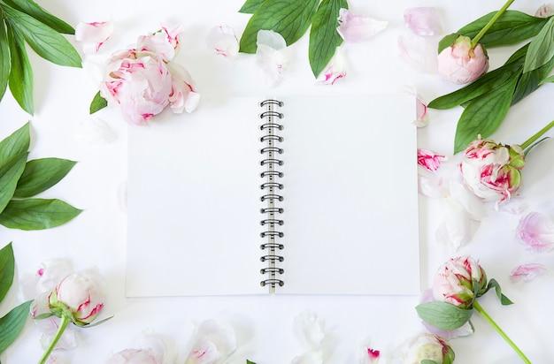Bloemen plat leggen pioenrozen en bloknotitie mockup-uitnodiging