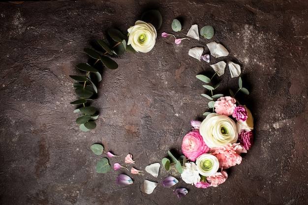 Bloemen rond frame met eucalyptustakken en bladeren, platliggende bloemen, bovenaanzicht met kopieerruimte