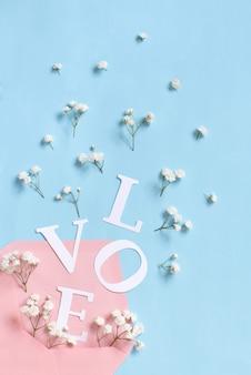 Bloemen, roze envelop en woord love op een lichtblauwe achtergrond bovenaanzicht