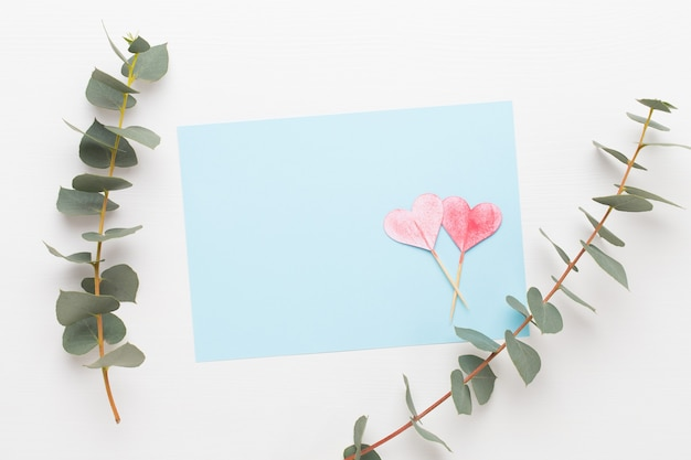 Bloemen samenstelling. blanco papier, bloemen, eucalyptustakken op pastel