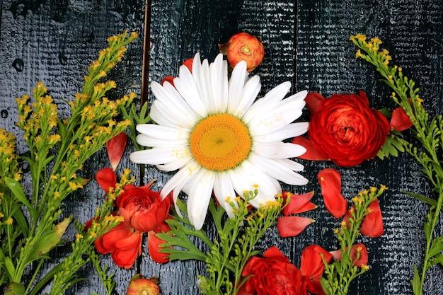 Bloemen samenstelling bovenaanzicht op donkere houten achtergrond oude stijl platte madeliefje ranunculus asiaticus