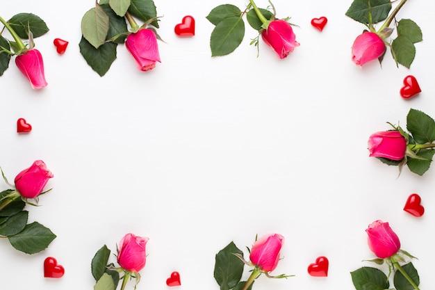 Bloemen samenstelling. frame gemaakt van rode roos op witte achtergrond. plat leggen, bovenaanzicht, kopie ruimte.