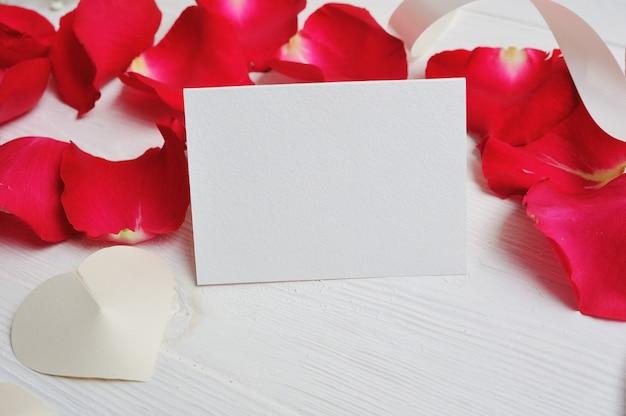 Bloemen samenstelling hart brief met rode rozenblaadjes