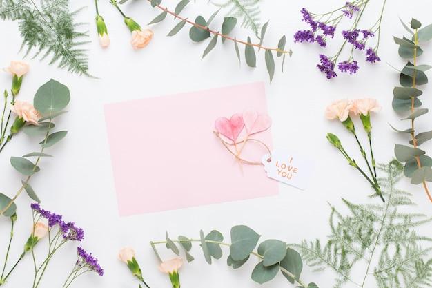 Bloemen samenstelling. papier blanco, anjerbloemen, eucalyptustakken op pastel achtergrond. plat lag, bovenaanzicht.