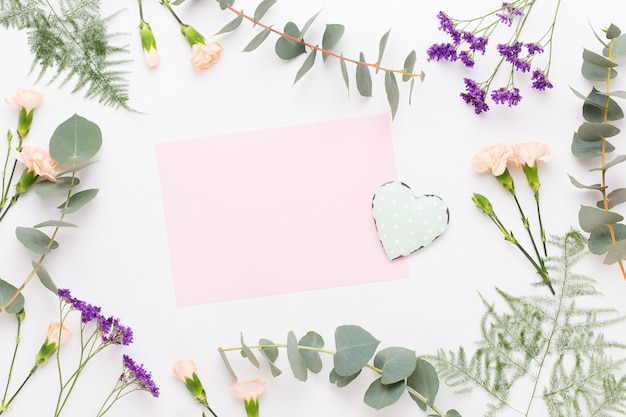 Bloemen samenstelling. papier blanco, anjerbloemen, eucalyptustakken op pastel
