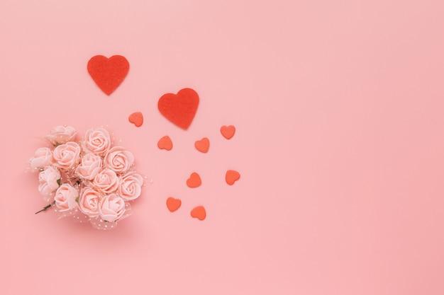 Bloemen samenstelling. patroon gemaakt van roze bloemen en harten op roze achtergrond.