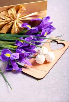 Bloemen, snoep en geschenkdoos op grijze tafel