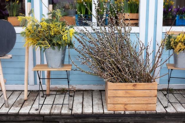 Bloemen te koop bij bloemenwinkel. houten veranda van huis met wilgentakken en bloemen gele mimosa. gezellig lenteterras. exterieur zomerveranda met bloemen. gevelhuis met paasdecor.