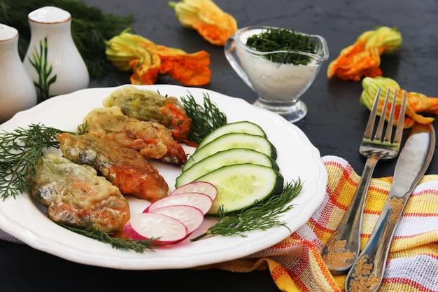 Bloemen van courgette, gekookt in beslag, plakjes komkommer en radijs op een bord