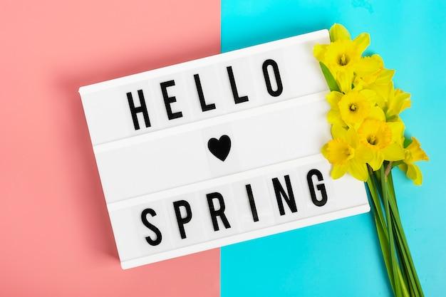 Bloemen van narcissen, lightbox met citaat hallo lente op blauwe, roze achtergrond