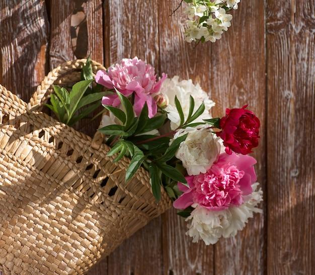 Bloemen van roze rode en witte pioenrozen in rieten mand op houten tafel tegen houten achtergrond
