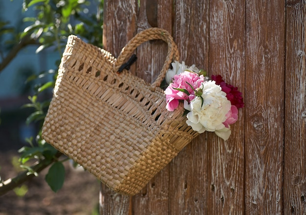 Bloemen van roze rode en witte pioenrozen in rieten mand op houten tafel tegen houten