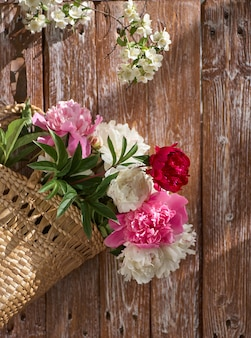 Bloemen van rozerode en witte pioenen in rieten mand op houten lijst tegen houten achtergrond