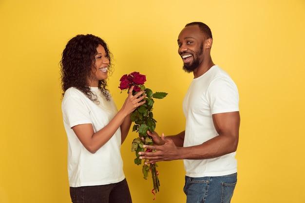 Bloemen voor een glimlach. valentijnsdagviering, gelukkig afrikaans-amerikaans paar dat op gele studioachtergrond wordt geïsoleerd. concept van menselijke emoties, gezichtsuitdrukking, liefde, relaties, romantische vakanties.